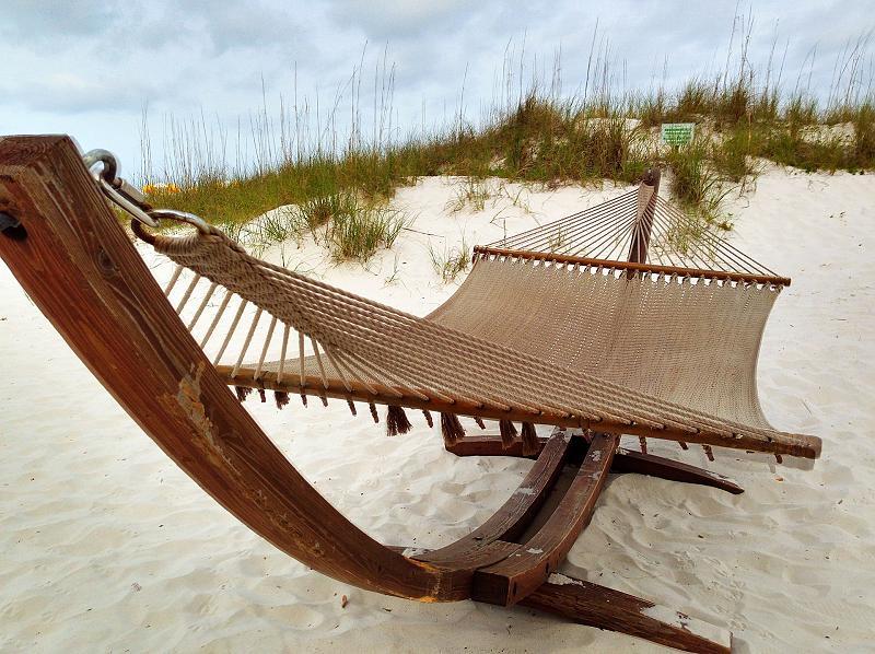 Houpací síť na dřevěné konstrukci stojí na pláži.