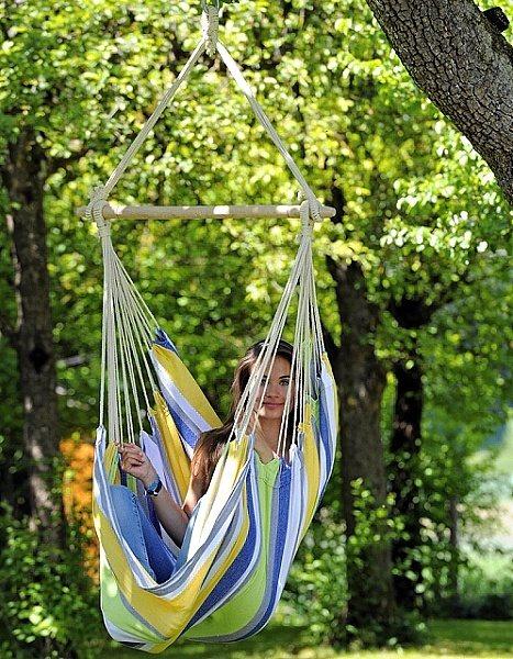 žena v látkovém závěsném křesle na stromě