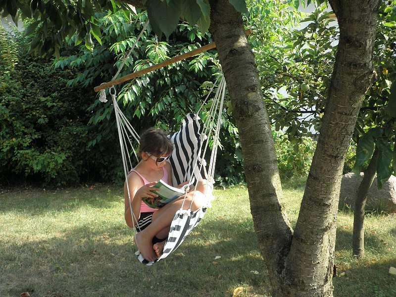 Závěsné křeslo visí na stromě a v něm si čte dívka.